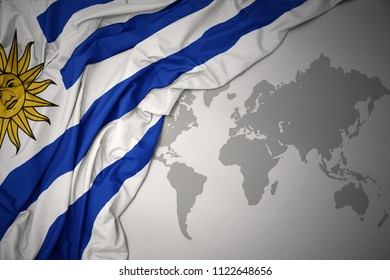waving colorful national flag of uruguay on a gray world map background.