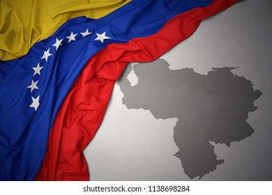 waving colorful national flag of venezuela on a gray map background.