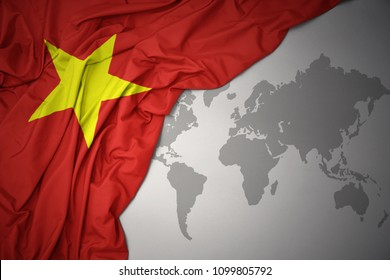 waving colorful national flag of vietnam on a gray world map background.