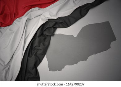 waving colorful national flag of yemen on a gray map background.