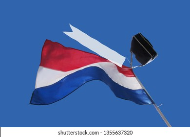Waving dutch flag, on blue sky, with school bag and blanc streamer in top, to celebrate graduation