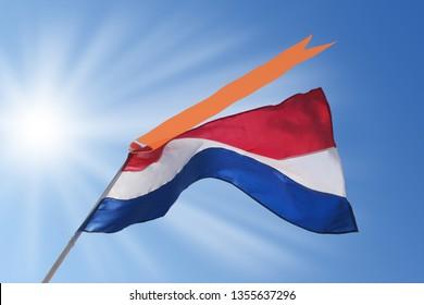 Waving dutch flag with orange streamer on blue, sunny sky. Koningsdag (Kingsday) and Bevrijdingsdag (Liberation Day) in the Netherlands.