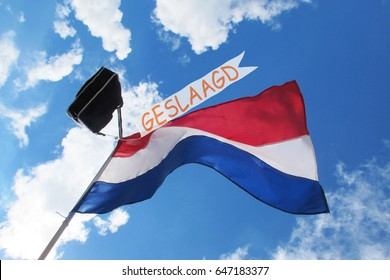 Waving dutch flag with school bag and banner in top, to celebrate graduation