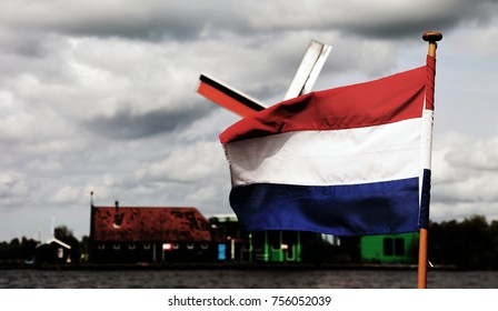 waving the Dutch flags and in the background the windmill the plumbean sky
