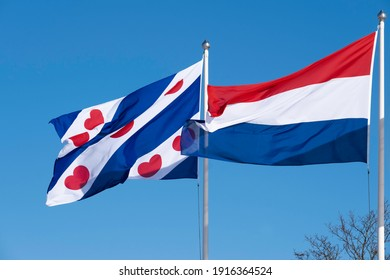 Waving Dutch and Frisian flag. The Frisian flag has four cobalt blue and three white diagonal stripes. The white strips have red pompoms. The Dutch flag is a horizontal tricolor in red, white and blue