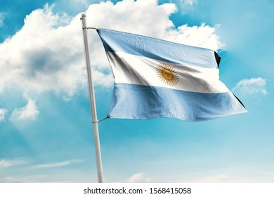 Waving Flag of Argentina in Blue Sky. Argentina Flag on pole for Independence day. The symbol of the state on wavy cotton fabric.