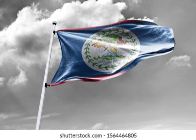 Waving Flag of Belize in Blue Sky. Belize Flag on pole for Independence day. The symbol of the state on wavy cotton fabric.