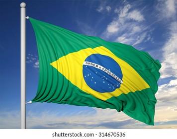 Waving flag of Brazil on flagpole, on blue sky background.