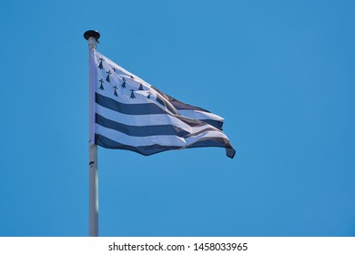 waving flag of Brittany against blue sky