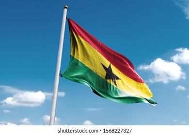 Waving Flag of Ghana in Blue Sky. Ghana Flag on pole for Independence day. The symbol of the state on wavy cotton fabric.