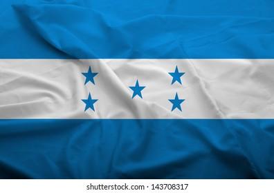 Waving flag of Honduras. Flag has real fabric texture.