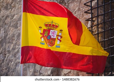 Waving flag of Spain hanging on the Kingdom of Spain institutions and administrative building in Alicante, Valencia, Spain