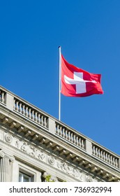 waving flag of Switzerland in the blue sky