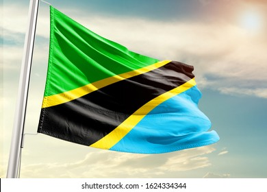 Waving Flag of Tanzania in Blue Sky. Tanzania Flag on pole for Independence day. The symbol of the state on wavy cotton fabric.