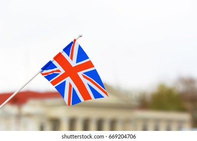 Waving flag of United Kingdom and blurred building on background