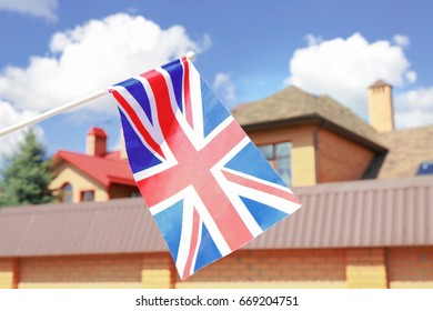 Waving flag of United Kingdom and blurred house on background