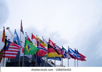 Waving flags of almost all countries on flagpoles on the top of the dutch house roof