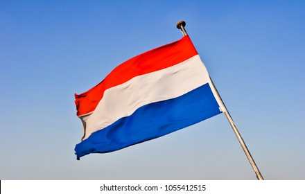 waving flags of Holland against the blue sky