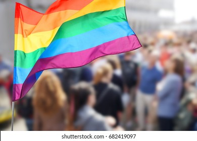 Waving gay flag and crowd of people on background. Concept of LGBT rights and parade