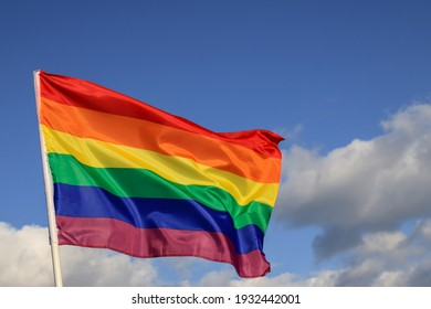 Waving gay pride rainbow flag in blue summer sky, copy space Realistic flag of LGBT organization  include lesbians, gays, bisexuals and transgender people.