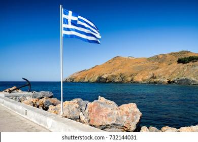 Waving greek flag on mast. resort Panormos in Crete island, Greece