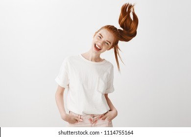 Waving hair so troubles flow away. Portrait of good-looking carefree caucasian woman with red hair, tilting head and smiling joyfully, having fun over gray background, holding hand in pocket