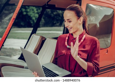 Waving hand. Businesswoman staying near her little private helicopter waving hand having video chat