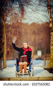 waving happy young adult woman on wheelchair in the park in winter at sunset