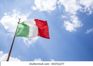 Waving Italian flag against blue sky, Rome, Italy