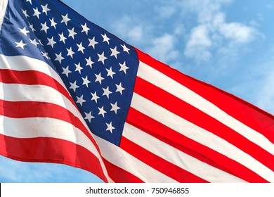 Waving star and stripes American flag on the blue sky