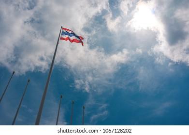 Waving thai flag on the tall flagpole against cloudy blue sky