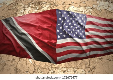 Waving Trinidadian and American flags on the of the political map of the world