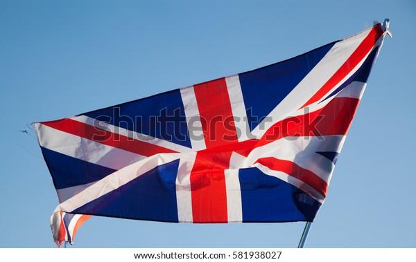 waving UK flag in the blue sky, Union Jack flag