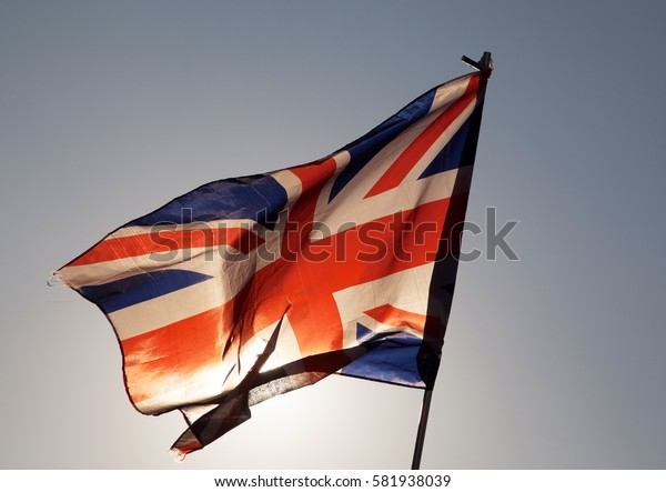 waving UK flag in the blue sky, Union Jack flag