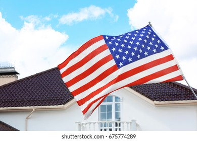 Waving USA flag and house roof with blue sky on background