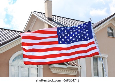 Waving USA flag and private house on background