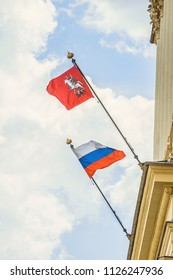 Waving in wind flag of the city of Moscow and the national flag of Russia installed on the cornice building