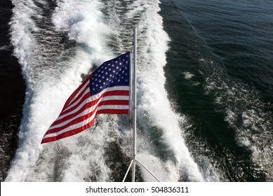 Waving in the wind US flag on the background of the ship wake