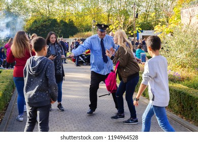 Wavre,Walibi park/ Belgium - October 14- 2017: a zombie policeman with a burned face catches people in the street during a halloween holiday. Horror performance in the park of attractions.