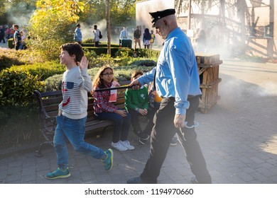 Wavre,Walibi park/ Belgium - October 14- 2017: a zombie policeman with a burned face catches a boy in the street during a halloween holiday. Horror performance in the park of attractions.