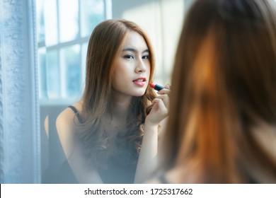 Wavy blong hair girl applying the red lipstick on her lip in sunlight.