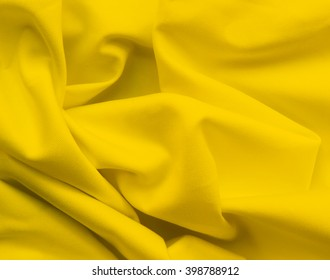 Wavy cloth or textile. Closeup of yellow texture.