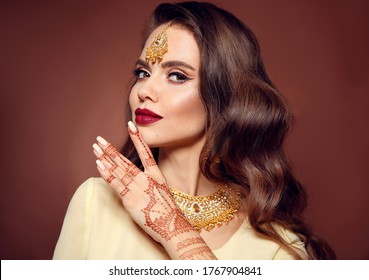 Wavy hair. Portrait of beautiful girl with indian jewelry. Young woman model with kundan golden bijouterie set. Traditional Indian costume lehenga. Mehendi Henna painting on hand.