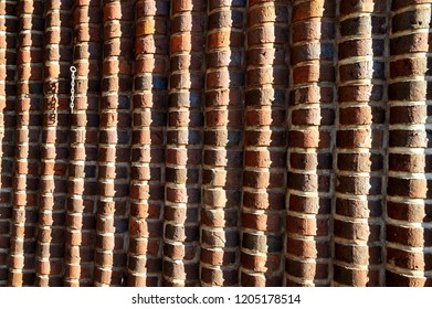 A wavy red brick wall outside on a sunny day with a small metal chain in the corner.
