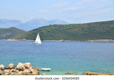 Wavy sea with sailing boat in bay, with hills in distance