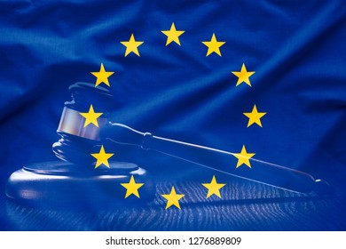 Wavy silk flag of European Union with court gavel or hammer for auction in background. EU judgement concept in full frame