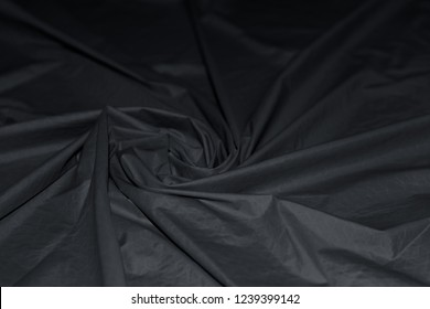 Wavy spiral folds of grunge nylon fabric. Abstract textile background of waterproof high quality nylon material.