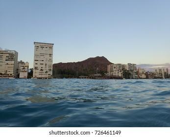 Wavy water on ocean off Kaimana Beach with hotels, condos, and Diamondhead line the shoreline at dusk on Oahu, Hawaii.
