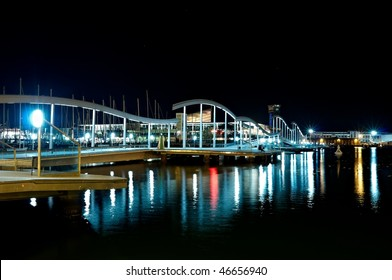 A wavy wooden walkway known as the Rambla de Mar (Rambla of the Sea) stretches out over the water of the port as far as the wharf opposite.