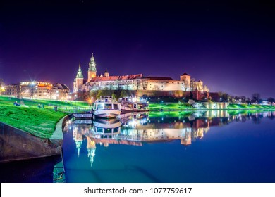 Wawel castle famous landmark in Krakow, Poland reflected on the surface of Vistula river at night.